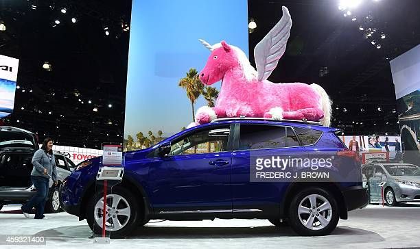 The 2015 Toyota RAV4 is displayed with a giant stuffedanimal unicorn on its roof on display at the LA Auto Show's press and trade day in Los Angeles...