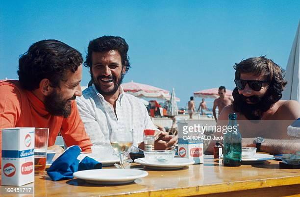 Louis Malle And Roman Polanski Le 21ème Festival de CANNES 1968 Louis MALLE barbu assis à une table à la plage avec un homme non identifié et Roman...