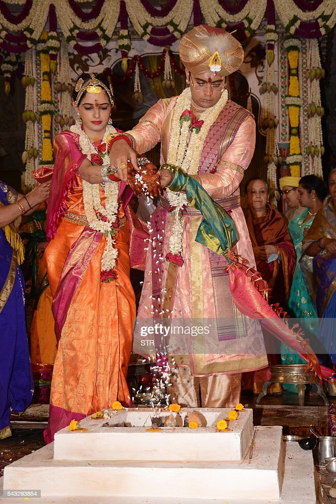 The 27th titular head of the Wodeyar dynasty, 24-year-old Yaduveer Chamraja Krishnadatta Wodeyar (R) and Trishika Kumari of the Dungarpur dynasty of Rajasthan perform rituals during their wedding ceremony at the Amba Vilas Palace in southern Mysore city on June 27, 2016. The royal wedding which happened after four decades, began with invocations to the royal family deity Hindu Goddess Chamundeshwari, as per the Wodeyar's dynastic traditions. / AFP / STR