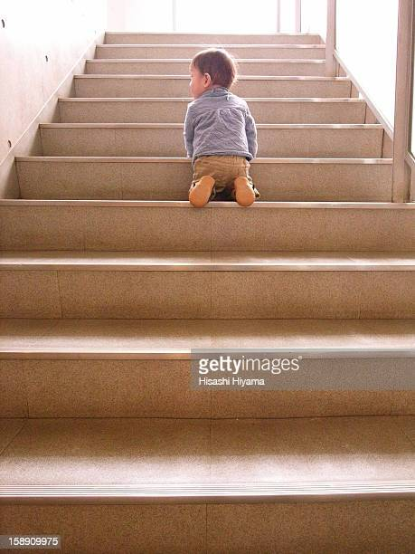 The 2-year-old boy who kneels in stairs.