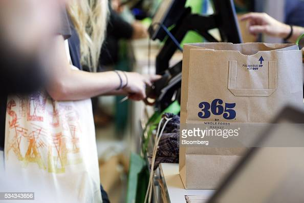 The 365 logo is displayed on a paper shopping bag as a customer checks out on the opening day of the 365 by Whole Foods Market store in the Silver...