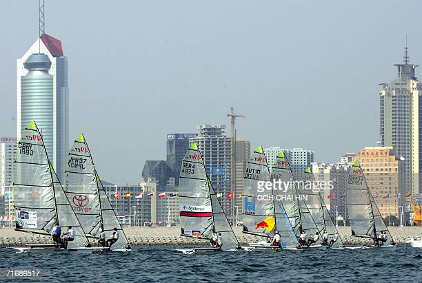 The 49er class eighteenfooter skiff race towards the finish line with the backdrop of the city on the first day of competition in China's largestever...