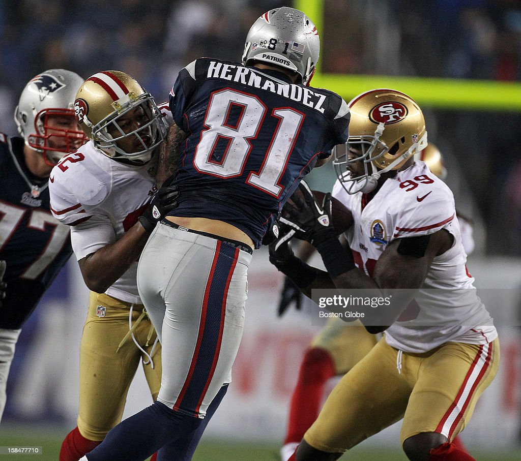The 49ers' Aldon Smith (#99), right, intercepts a pass intended for Patriots tight end Aaron Hernandez (#81) as the New England Patriots hosted the San Francisco 49ers in a Sunday night NFL game at Gillette Stadium.