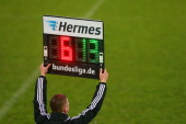 The 4th official referee holds the referee board with substitution numbers during the Second Bundesligamatch between Jahn Regensburg and FC...