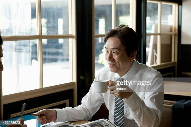 The 50th generation male businessman who drinks coffee
