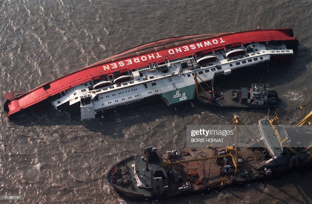 The 7,951-ton roll-on-roll-off British car ferry the Harald of Free Enterprise belonging to Townsend Thoresen lays on its side off the Belgian port of Zeebrugge 07 March 1987 surrounded by rescue boats. Two hundred cross channel passengers were feared dead in the night of 06 March after the ferry capsized in waters off Zeebrugge. The ferry rolled over and sank a mile outside the port. First indications were that the bow doors were open enabling water to pour into the car deck. The ferry had just left the port around 7,00pm bound for Dover when she sank, leaving on third of the hull still above water. The disaster happened so swiftly there wasn't time to send an SOS.