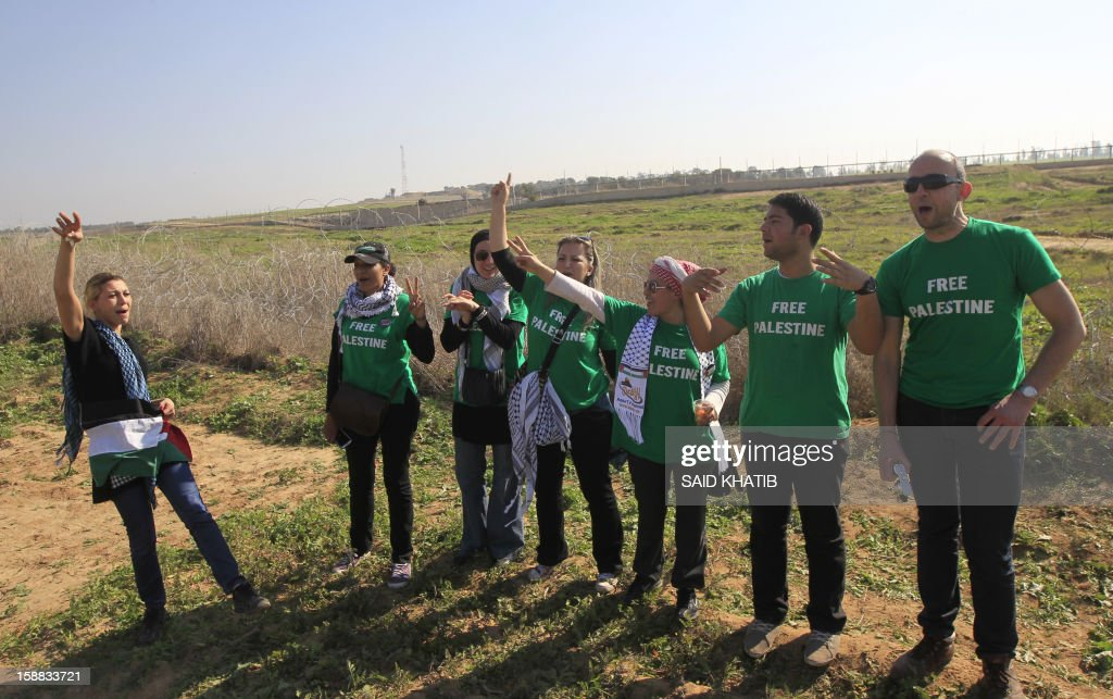 The 87 member delegation of mostly French and Egyptian pro-Palestinian activists, shout slogans against Israel during their visit in support of Palestinian farmers next to the security fence standing on the Gaza border with Israel, east of Gaza city on December 31, 2012. The mission 'Welcome to Palestine' aims to denounce the blockade of the Palestinian territory that was imposed in June 2006. AFP PHOTO/ SAID KHATIB