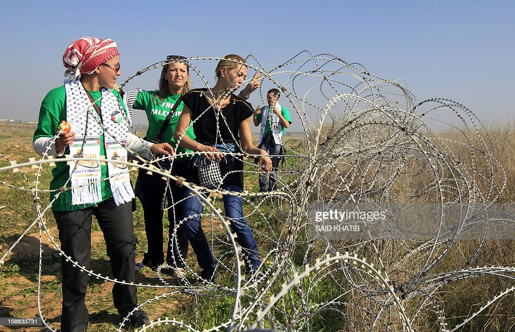 The 87 member delegation of mostly French and Egyptian pro-Palestinian activists, pull at razor wire during their visit in support of Palestinian farmers next to the security fence standing on the Gaza border with Israel, east of Gaza city on December 31, 2012. The mission 'Welcome to Palestine' aims to denounce the blockade of the Palestinian territory that was imposed in June 2006. AFP PHOTO/ SAID KHATIB