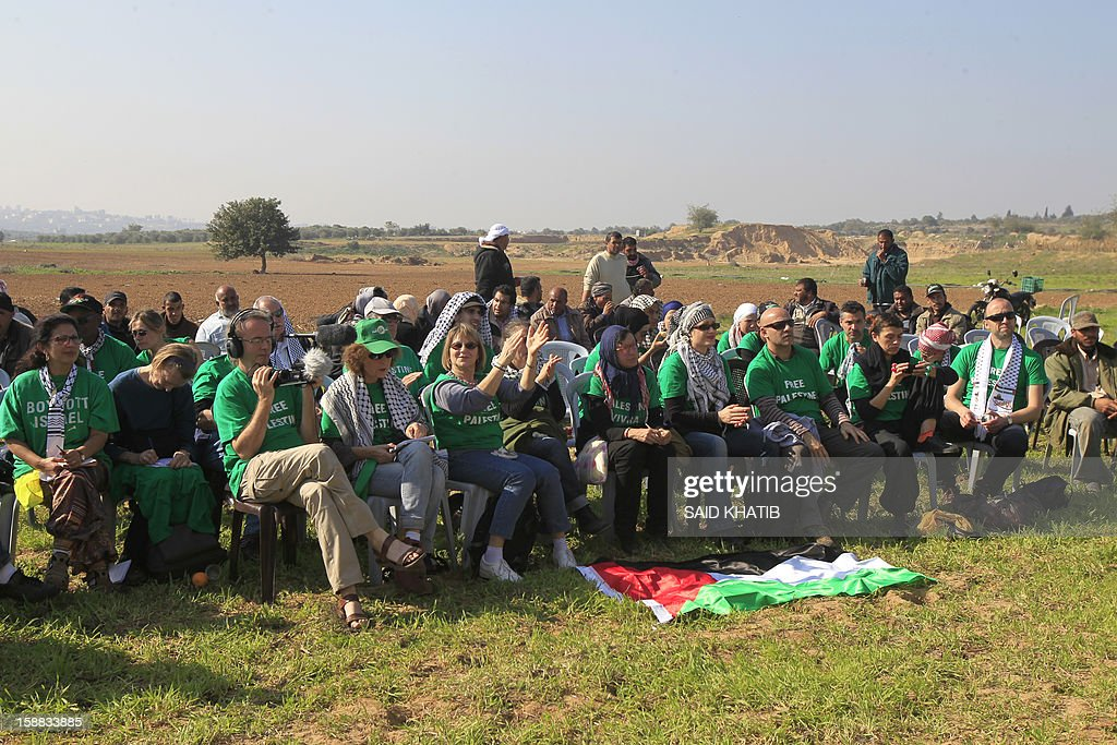 The 87 member delegation of mostly French and Egyptian pro-Palestinian activists, protest against Israel during their visit in support of Palestinian farmers next to the security fence standing on the Gaza border with Israel, east of Gaza city on December 31, 2012. The mission 'Welcome to Palestine' aims to denounce the Israeli blockade of the Palestinian territory that was imposed in June 2006. AFP PHOTO/ SAID KHATIB
