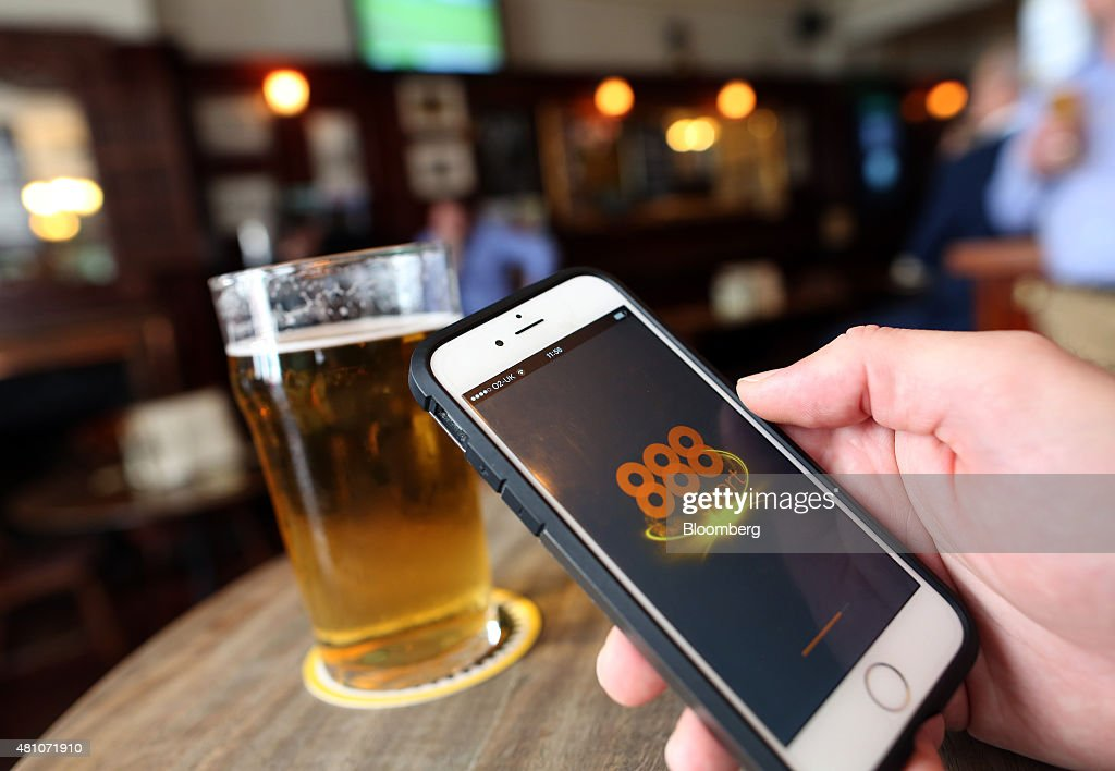 The 888 Holdings Plc sports betting app homepage sits on an Apple Inc. iPhone 6 beside a pint of beer in this arranged photograph taken in London, U.K., on Friday, July, 17, 2015. 888 Holdings Plc agreed to buy Bwin.party Digital Entertainment Plc for 898.3 million-pounds ($1.4 billion) in cash and shares, winning over the online gaming company that's been at the center of a takeover battle. Photographer: Chris Ratcliffe/Bloomberg via Getty Images