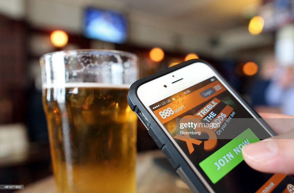 The 888 Holdings Plc sports betting app sits on an Apple Inc. iPhone 6 beside a pint of beer in this arranged photograph taken in London, U.K., on Friday, July, 17, 2015. 888 Holdings Plc agreed to buy Bwin.party Digital Entertainment Plc for 898.3 million-pounds ($1.4 billion) in cash and shares, winning over the online gaming company that's been at the center of a takeover battle. Photographer: Chris Ratcliffe/Bloomberg via Getty Images