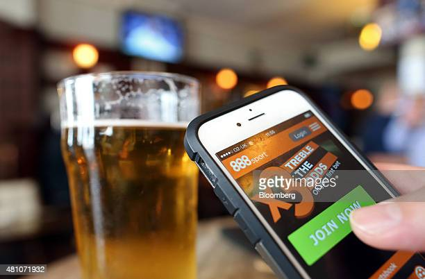The 888 Holdings Plc sports betting app sits on an Apple Inc iPhone 6 beside a pint of beer in this arranged photograph taken in London UK on Friday...