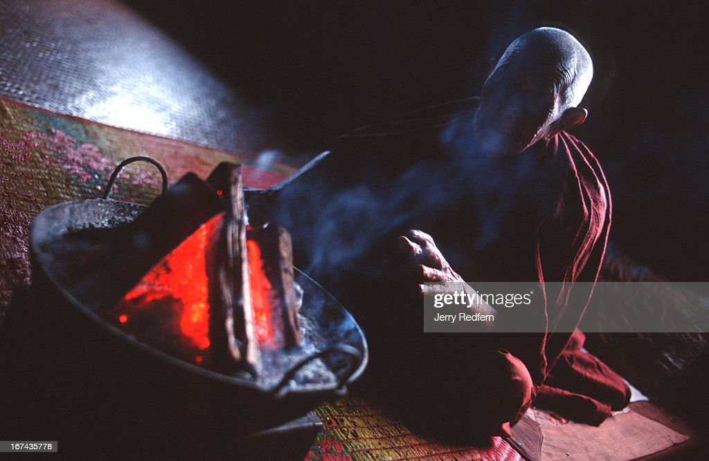 The 90-year-old head monk at the Buddhist monastery in Pat Tu Paut warms his hands over a brazier before eating his breakfast..