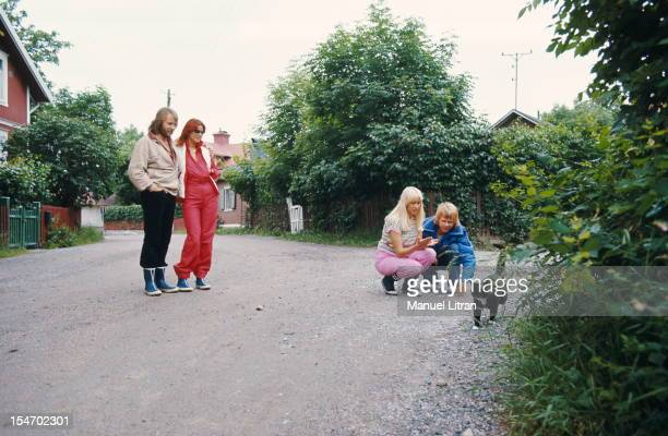 The ABBA posing in a street of a village with AnniFrid Lyngstad and her husband Benny Andersson Agnetha Faltskog and watching her husband Bjorn...