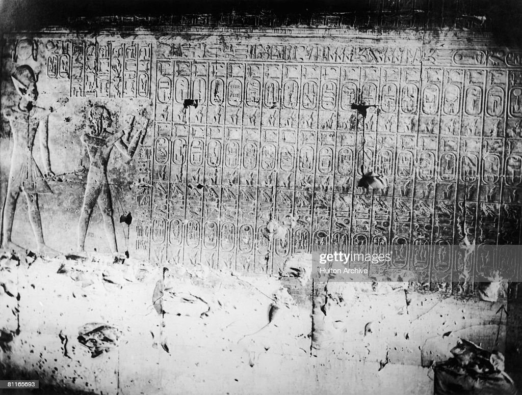 The Abydos King List or Abydos Table on the walls of the Temple of Seti I at Abydos, Egypt, circa 1930. On the list are the names of seventy-six kings and pharaohs of ancient Egypt, and worshipping them on the left are the figures of Seti I and his son Ramses II.