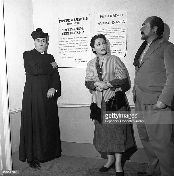 The actor Fernandel standing beside a man and a woman during a break on the set of the film Don Camillo's Last Round Behind them two notice posters...