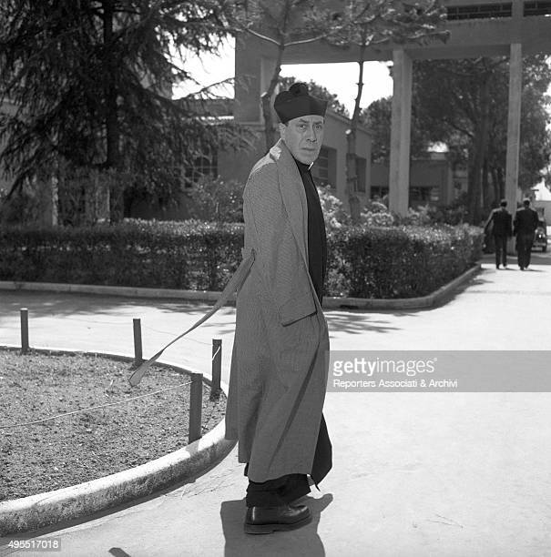 The actor Fernandel walking in cassock and coat in a garden during a break on the set of the film Don Camillo's Last Round 1955