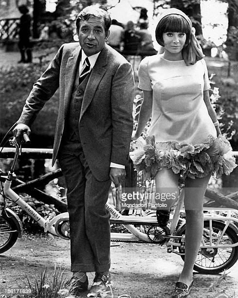 The actor Ugo Tognazzi and the dancer and singer Maria Grazia Buccella pose next to a tandem bycicle on the set of the movie Dismissed on His Wedding...