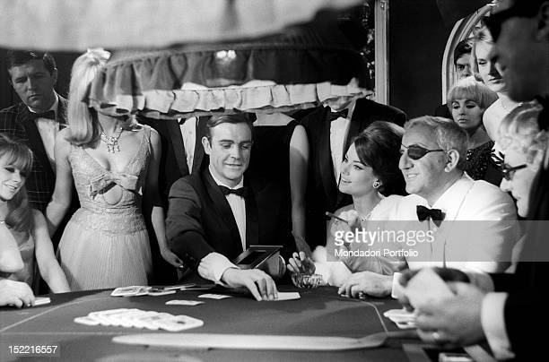 The actors Sean Connery Claudine Auger and Adolfo Celi prepare the scene at the casino from the movie Thunderball by Terence Young fourth episode of...