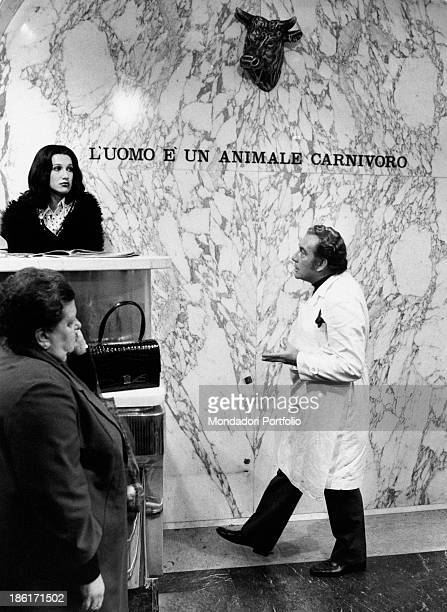 The actors Ugo Tognazzi and Daria Nicolodi as the rich butcher and his lover Anita in the butcher shop whose wall has printed on the inscription The...