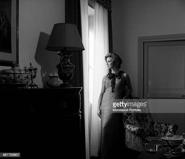 The actress Ilaria Occhini wearing a stylish long dress with lace collar in the middle of the sitting room of her tasteful Roman flat looks out of...