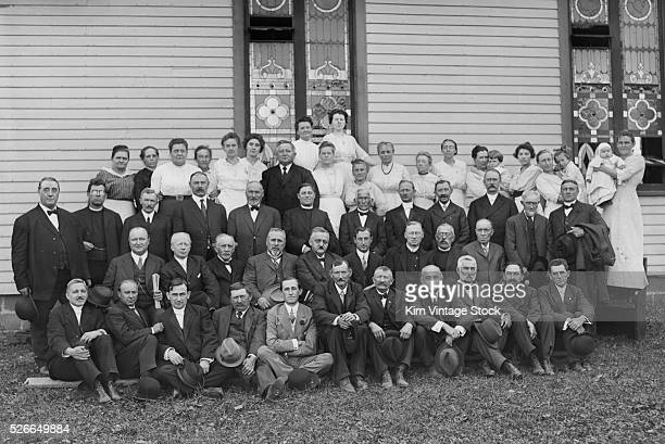 The adult members of a Germanspeaking church pose outside for a group portrait