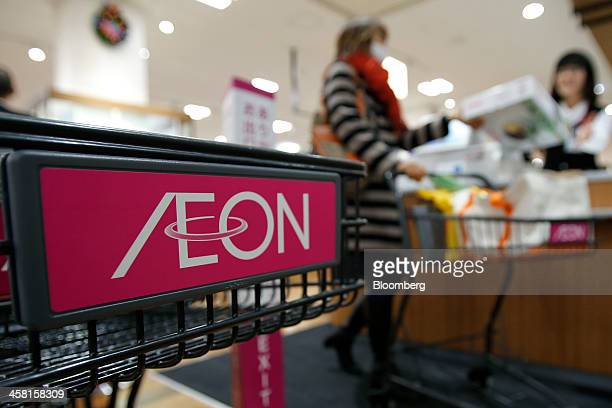 The Aeon Co logo is displayed on a shopping cart while a customer checks out at the Aeon Style Store in the Aeon Mall Makuhari Shintoshin shopping...