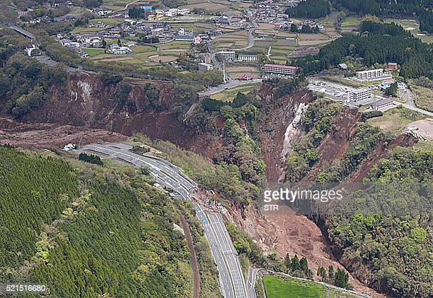 The aerial view shows a landslide after an earthquake in MinamiAso Kumamoto prefecture on April 16 2016 Scores of people were feared buried alive...