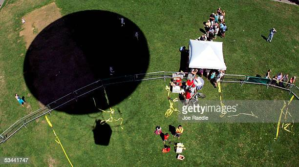 The AeroBalloon USA's giant helium balloon casts a shadow on the ground as people wait in line for a ride at the Boston Commons August 19 2005 in...