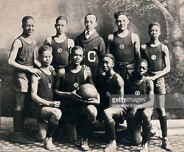 The African American basketball team at Oliver High School and their coach EJ Hooper lined up for a portrait Winchester Kentucky circa 1921