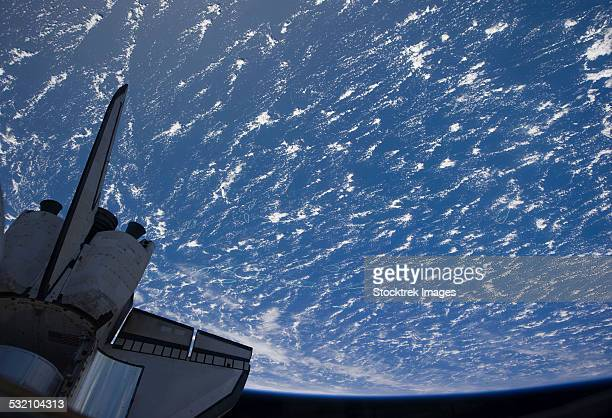The aft section of space shuttle Discovery backdropped by planet Earth.