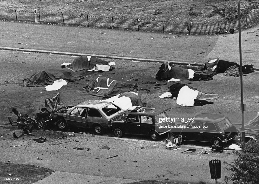The aftermath of a Provisional IRA car bombing, which killed five soldiers and seven horses on South Carriage Drive in Hyde Park, London, 20th July 1982. The seven dead horses lie in the road under sheets.