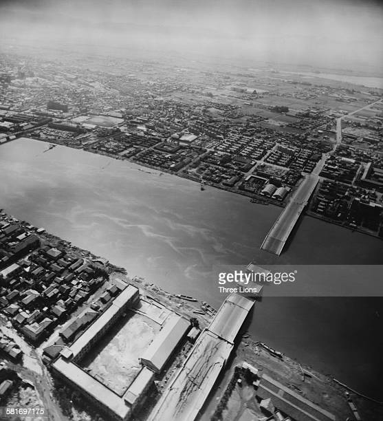 The aftermath of an earthquake in Niigata Honshu Japan showing the wreckage of a bridge across the Shinano River June 1964 The resulting tidal wave...