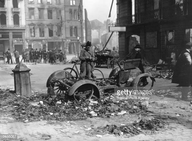 The aftermath of the Easter uprising with the ruins of a car in the foreground which has been used as a barricade Men are standing around on street...
