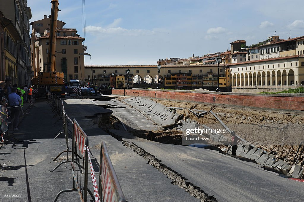 The aftermath of where a road collapsed along the Arno river is seen on May 25, 2016 in Florence, Italy. The deterioration of one or more water pipes opened a 200 m wide and 7m deep hole on Wednesday morning along the bank of the river Arno close to the famous Ponte Vecchio bridge. Many cars that were parked sunk and damages are thought to be around 5 millions euros.