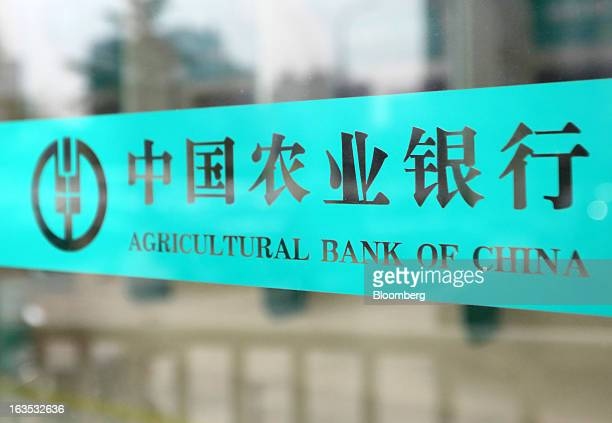 The Agricultural Bank of China Ltd logo is displayed on a glass door at one of the bank's branches in Beijing China on Monday March 11 2013 China's...