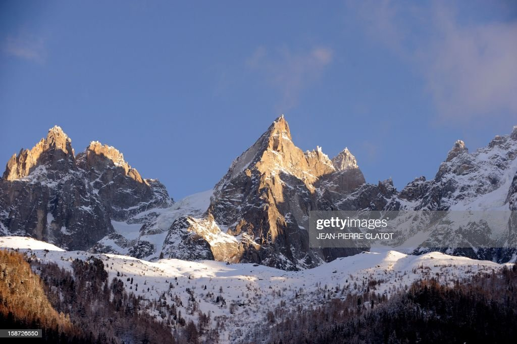 The 'Aiguilles de Chamonix' in the Mont-Blanc mountain chain are pictured on December 26, 2012 behind the frozen Gailland lake in the Chamonix valley, French Alps. AFP PHOTO / Jean Pierre Clatot