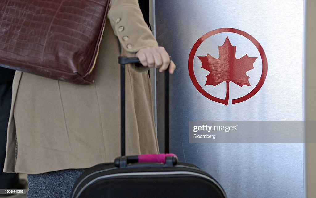 The Air Canada logo is seen next to a check-in area at Pearson International Airport in Toronto, Ontario, Canada, on Wednesday, Feb. 6, 2013. Air Canada, the country's biggest carrier, is scheduled to announce quarterly earnings data on Feb. 7. Photographer: Aaron Harris/Bloomberg via Getty Images
