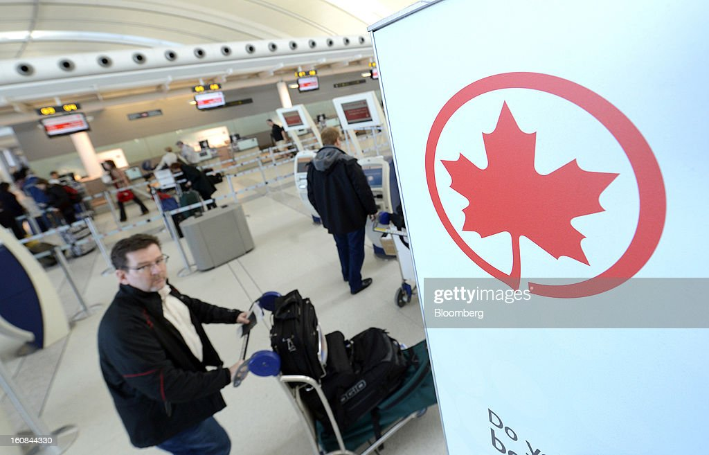 The Air Canada logo is seen next to a check-in line at Pearson International Airport in Toronto, Ontario, Canada, on Wednesday, Feb. 6, 2013. Air Canada, the country's biggest carrier, is scheduled to announce quarterly earnings data on Feb. 7. Photographer: Aaron Harris/Bloomberg via Getty Images