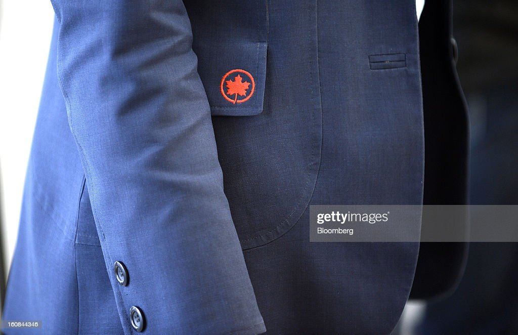 The Air Canada logo is seen on an employee's uniform at Pearson International Airport in Toronto, Ontario, Canada, on Wednesday, Feb. 6, 2013. Air Canada, the country's biggest carrier, is scheduled to announce quarterly earnings data on Feb. 7. Photographer: Aaron Harris/Bloomberg via Getty Images