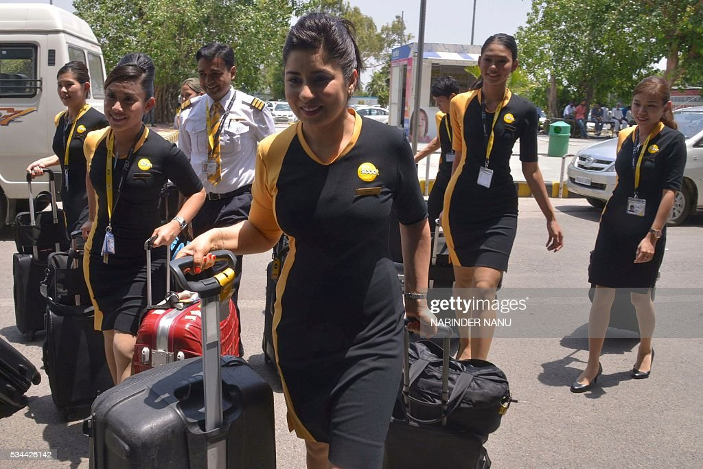 The air crew for Scoot, Singapore Airlines' low-cost airline, walk to the departures area of Sri Guru Ramdas International Airport, as they fly from Amritsar to Singapore, in Amritsar on May 26, 2016. Scoot's India head Bharath Mahadevan said the airline launched its direct flight services to Singapore from Amritsar, which fly three days a week, from 24 May. / AFP / NARINDER
