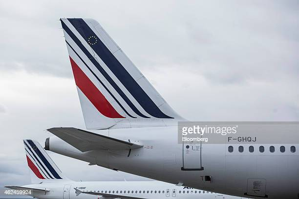The Air France logo sits on the tail fins of passenger planes operated by Air FranceKLM Group as they stand on the tarmac at ToulouseBlagnac airport...