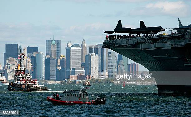The aircraft carrier USS Intrepid is towed in by tugboats past lower Manhattan enroute to her dock at Pier 86 on the west side of Manhattan October 2...
