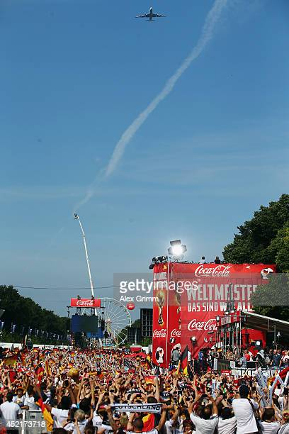 The airplane with the German national on board flies over the Fanmeile at Brandenburg Gate during the German team victory ceremony on July 15 2014 in...