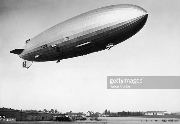 The airship Hindenburg marked with Nazi swastikas and Olympic rings in flight over Friedrichshafen Germany