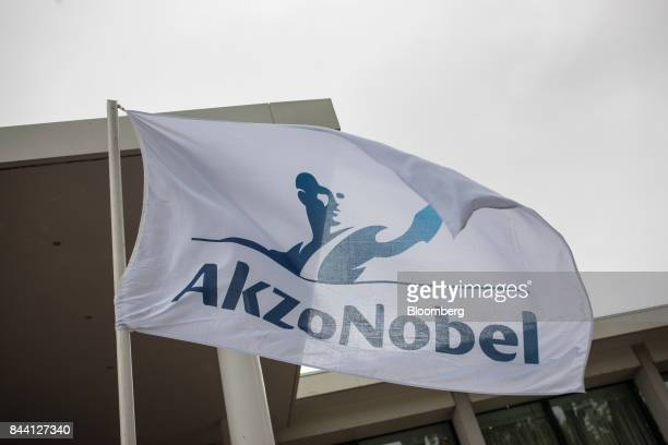 The Akzo Nobel NV logo sits on a flag flying outside the Hilton Amsterdam Hotel the venue of the company's shareholder meeting in Amsterdam...