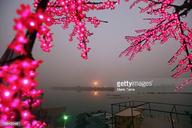 The Al Doura oil refinery is seen on the banks of the Tigris River as electric lights from a restaurant shine on December 10 2011 in Baghdad Iraq...