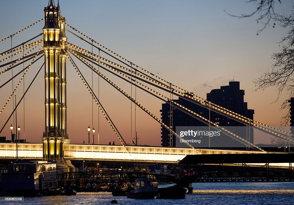 The Albert Bridge stands illuminated at night in front of residential apartments on the River Thames in London, U.K., on Sunday, March 3, 2013. Central London luxury-home prices unexpectedly rose at the fastest pace in 10 months in February as the British pound's depreciation helped attract international investors, Knight Frank LLP said. Photographer: Jason Alden/Bloomberg via Getty Images