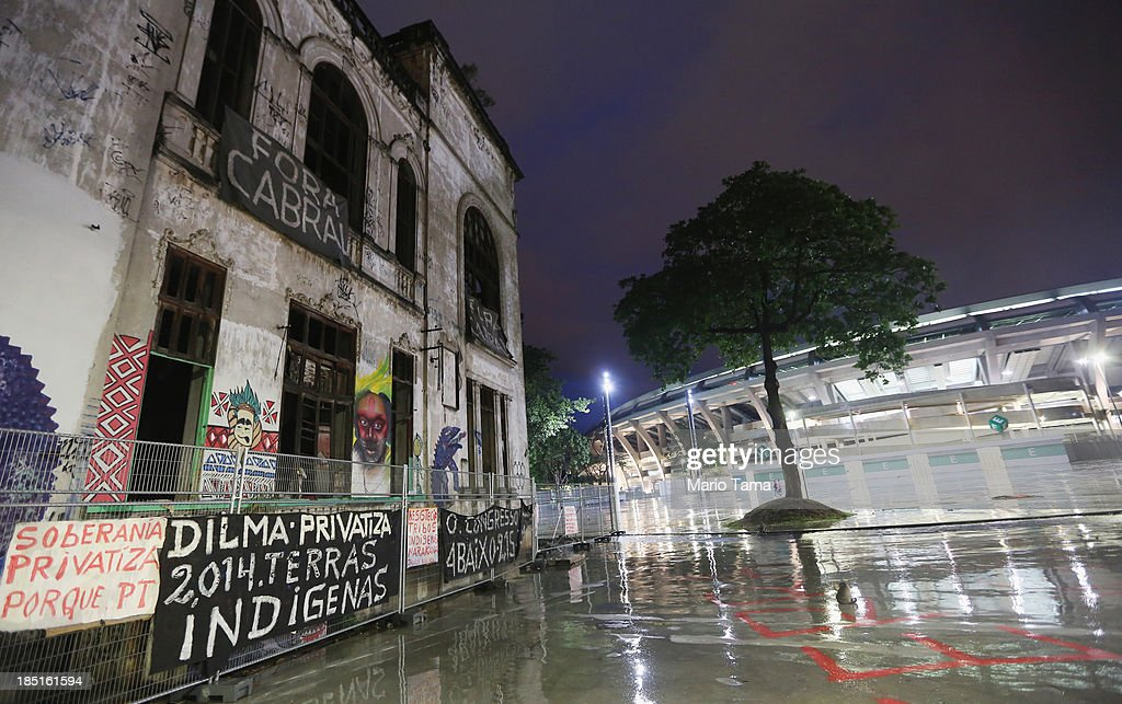The Aldeia Maracana building (L) being occupied by an indigenous community stands next to Maracana Stadium (R), the site of the 2014 World Cup finals, on October 17, 2013 in Rio de Janeiro, Brazil. The fading Aldeia Maracana used to house the Museum of Indian Culture before deteriorating and becoming occupied by squatting indigenous members in 2006. The building was slated for destruction ahead of the 2014 World Cup and the community was forcibly evicted in March. However, the community has managed to return and thus far have successfully battled to save the structure, which they hope to convert into an indigenous university. Indigenous groups throughout Brazil are battling the Brazilian government over land rights and other issues.