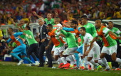 The Algeria bench celebrates after a 11 draw during the 2014 FIFA World Cup Brazil Group H match between Algeria and Russia at Arena da Baixada on...